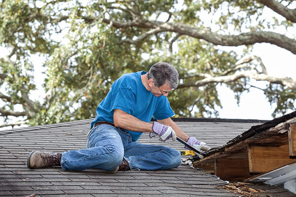 Man using crowbar to remove rotten wood from leaky roof.