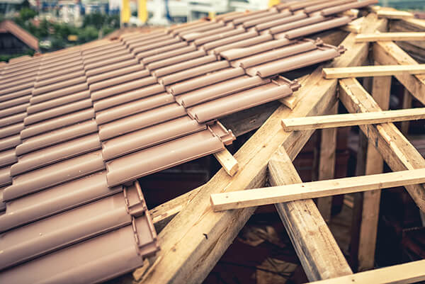 Construction site of new house roof building with brown tiles and timber