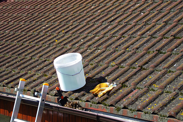 Cleaning materials above an old and dirty roof