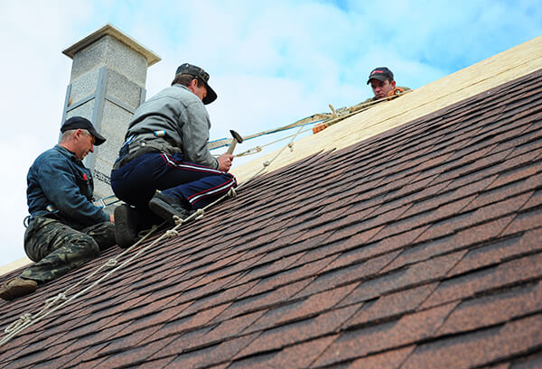 workers reroofing a house