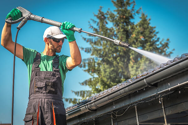 man uses a pressure washer to clean the roof